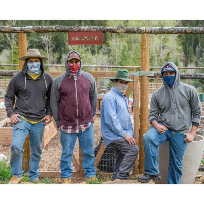 four men wearing different gaiters standing in front of a garden fence