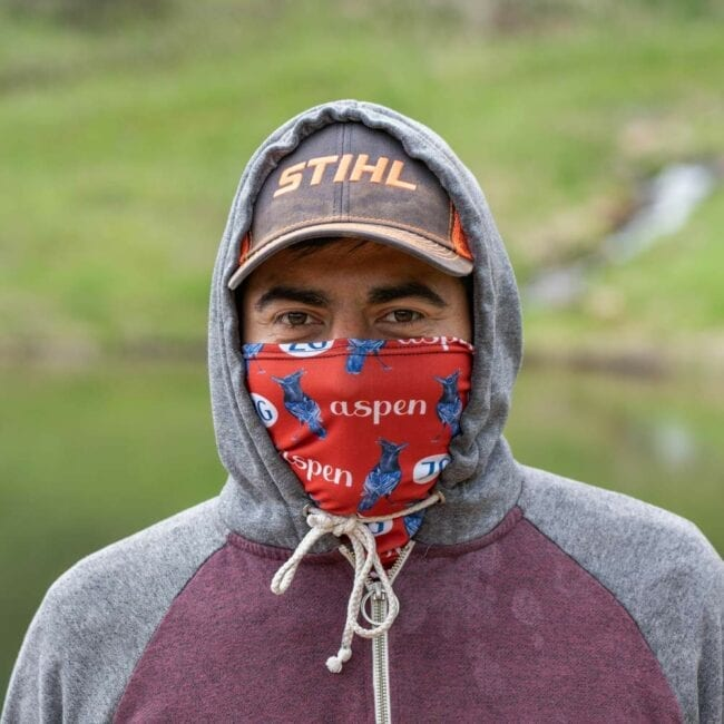 man wearing a red gaiter with a white aspen zg design and a steller's jay with a gray and maroon sweater with his hood on over his black and orange hat