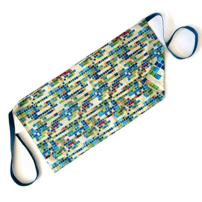 colorful geometric squares waist apron with tan, red, blue, and green and a blue ties with a reversible design of a larger scale