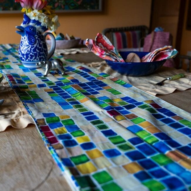 large scale colorful geometric squares designed table runner laid across an indoor table with a vase of yellow daffodils, and a small table setting with tan colored placemats and colorful napkins