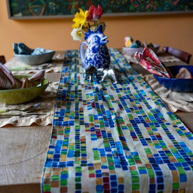 small scale of colorful geometric squares designed table runner laid across an indoor table with a vase of yellow daffodils, and a small table setting with tan colored placemats and colorful napkins