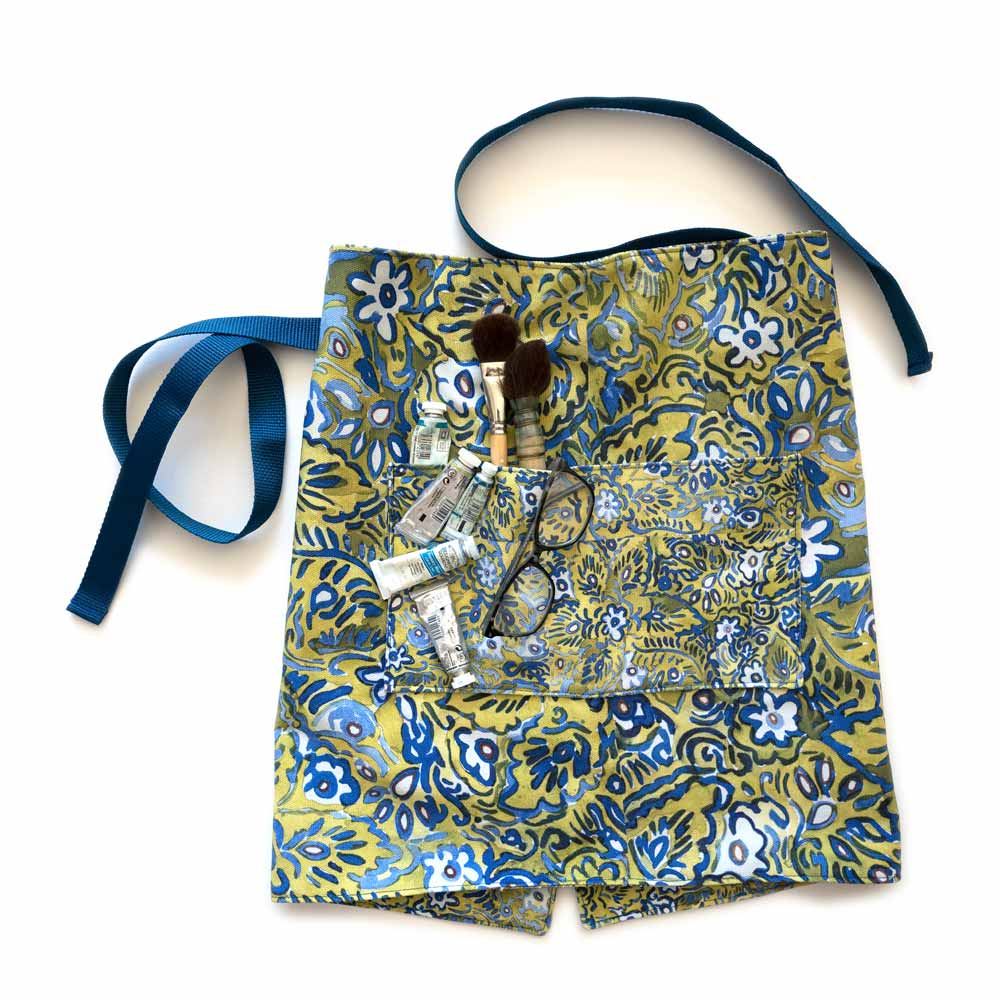 green and blue floral waist apron with paint brushes and watercolor and glasses in the pocket