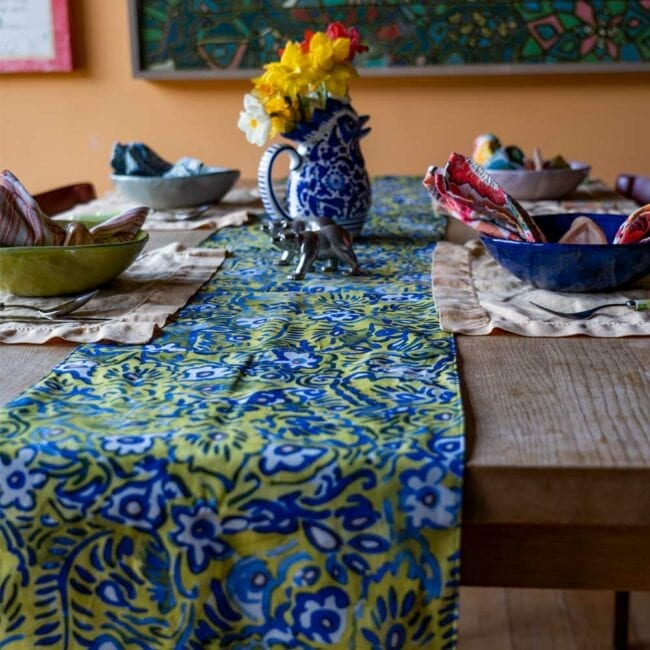 green and blue floral designed table runner laid across an indoor table with a vase of yellow daffodils, and a small table setting with tan colored placemats and colorful napkins