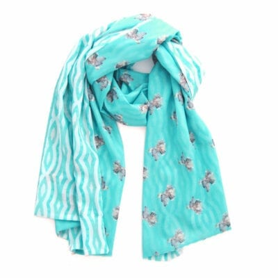 turquoise blue scarf with a hummingbird pattern on one side and hand illustrated wavy lines on the reverse