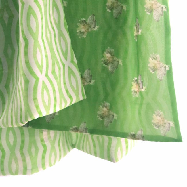 a close up view of the delicate transparency of this double-layer chiffon scarf; detail shows hand painted hummingbirds against an apple green background with green wavy lines on the reverse
