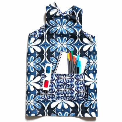 flat lay of a colorful reversible over the head smock for children to wear during activities each side includes a large pocket for supplies. pattern blue indigo shapes inspired by the garden lotus
