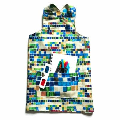 flat lay of a colorful reversible over the head smock for children to wear during activities each side includes a large pocket for supplies. pattern is green, blue and red watercolor squares