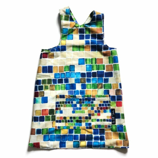 flat lay of a colorful reversible over the head smock for children to wear during activities each side includes a large pocket for supplies. alternate side has larger red, green, blue squares