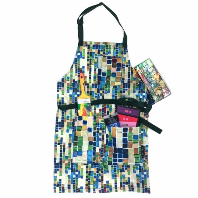 colorful geometric pattern apron with art supplies in the pockets; straps are blue webbing