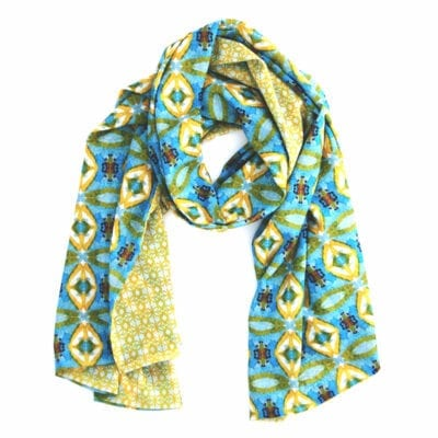 double sided chiffon scarf with a delicate yellow geometric pattern on one side and a graphic blue, yellow and red garden inspired pattern on the reverse