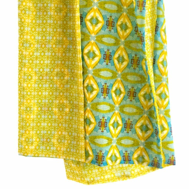 detail shot showing the transparency of a double sided chiffon scarf; one side is a detailed yellow geometric pattern the other is turquoise red and yellow abstracted geometric designs inspired by a garden