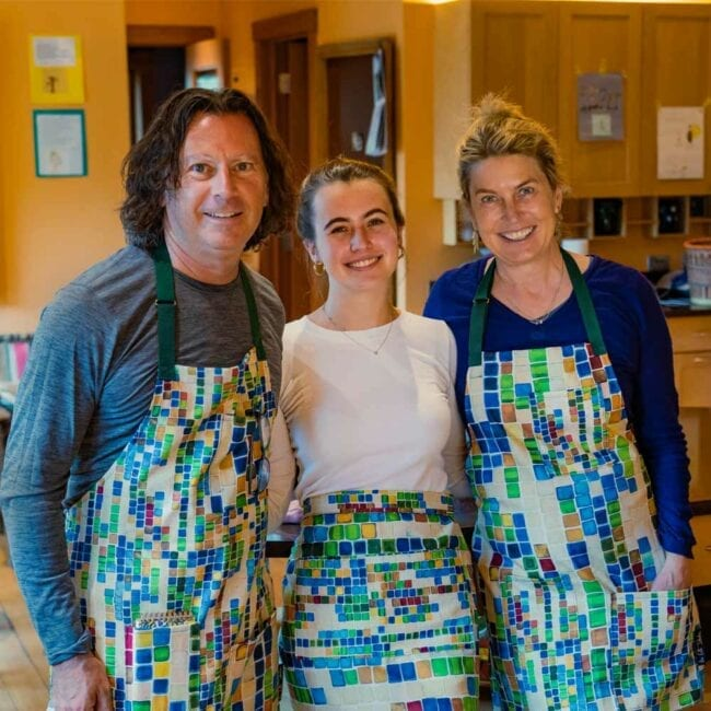 mother, father, and daughter wearing matching geometric squares aprons with different scales