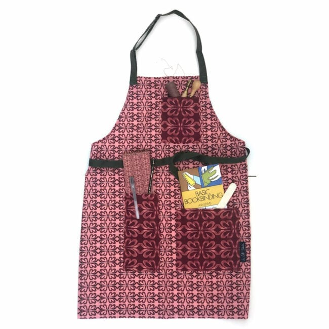Cloverleaf patterned apron in pink with bookbinding items in the pockets including an instruction manual, bonefolder, awl and notebook