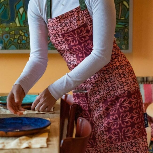 woman wearing a red earth tone apron setting a dinner table