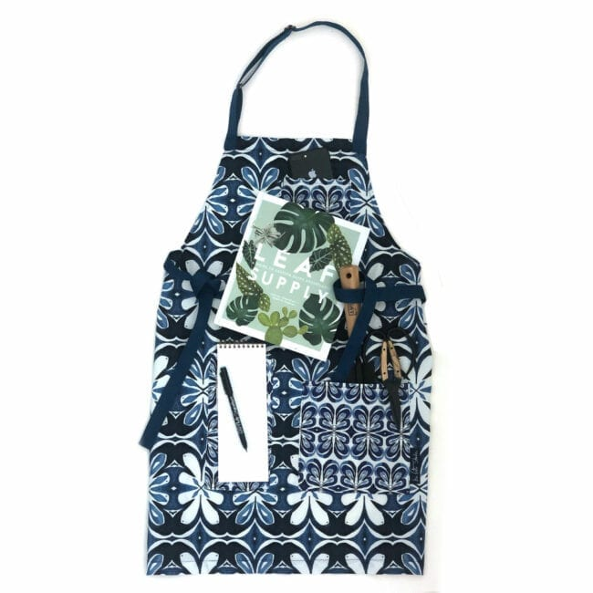 indigo patterned apron with gardening tools protruding from the pockets and a plant book on top