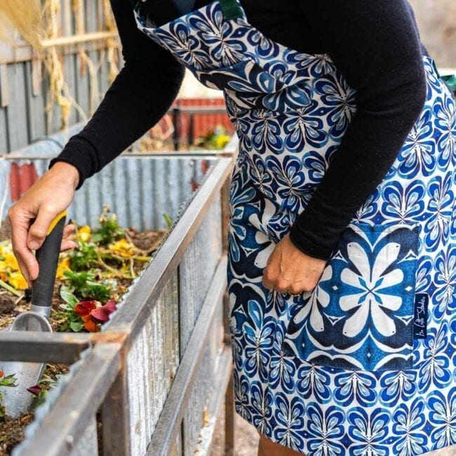 woman wearing a blue and white botanical apron while planting flowers