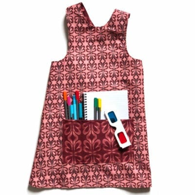 flat lay of a colorful reversible over the head smock for children to wear during activities each side includes a large pocket for supplies. pattern is pink and red clay cloverleaf patterns.
