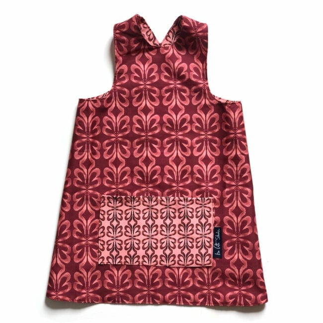 flat lay of a colorful reversible over the head smock for children to wear during activities each side includes a large pocket for supplies. pattern is pink and red clay cloverleaf patterns. Pocket is generously sized and shows the reverse fabric.