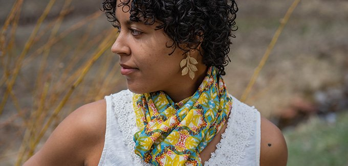 young woman wearing colorful scarf with abstract garden inspired design including turquoise, yellow and red patterns