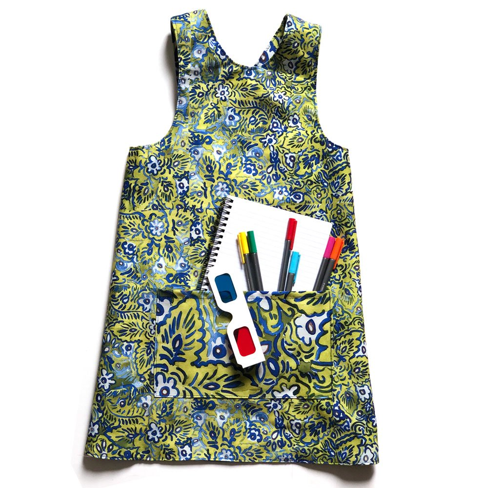 flat lay of a colorful reversible over the head smock for children to wear during activities each side includes a large pocket for supplies. pattern is green, white and blue floral design