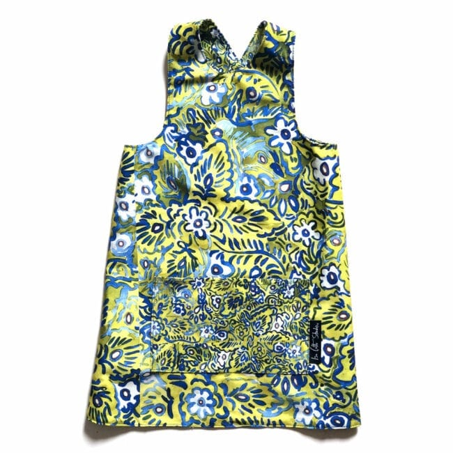 flat lay of a colorful reversible over the head smock for children to wear during activities each side includes a large pocket for supplies. pattern is green, white and blue floral design; pocket shows smaller scale design.