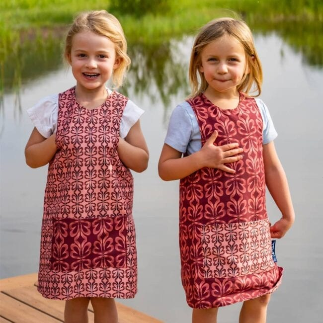 two girls standing on a pond dock wearing pink and red botanical patterned, earth tone matching smocks