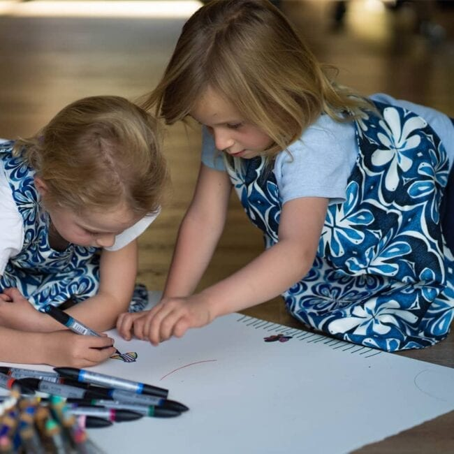 two girls wearing blue and whitebotanical and floral matching smocks while painting