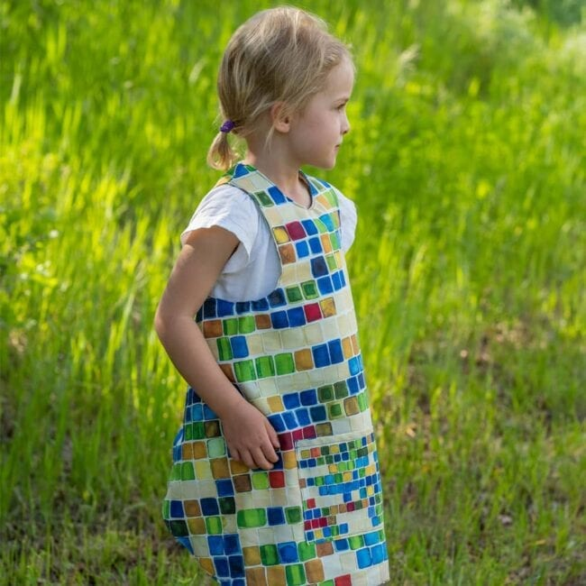 small blonde girl with pig tails wearing a colorful geometric squares smock looking out across a field