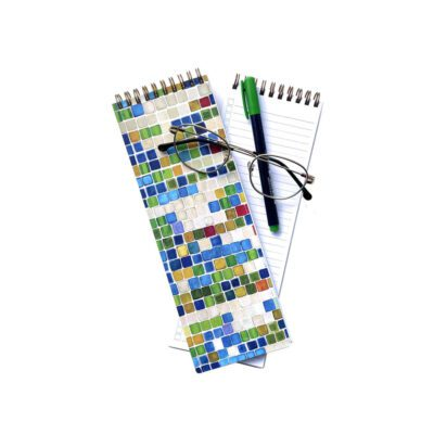 blue, green, and red squares organizational notebook with a green pen and gold glasses showing the inside sheets