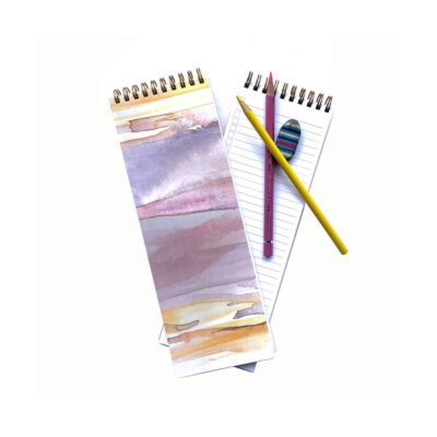 pink and gold sunset notebook cover with yellow and pink pencils and eraser showing inside cover