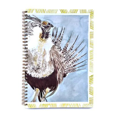 grouse with a gray sky background and a sage brush border on a wire notebook