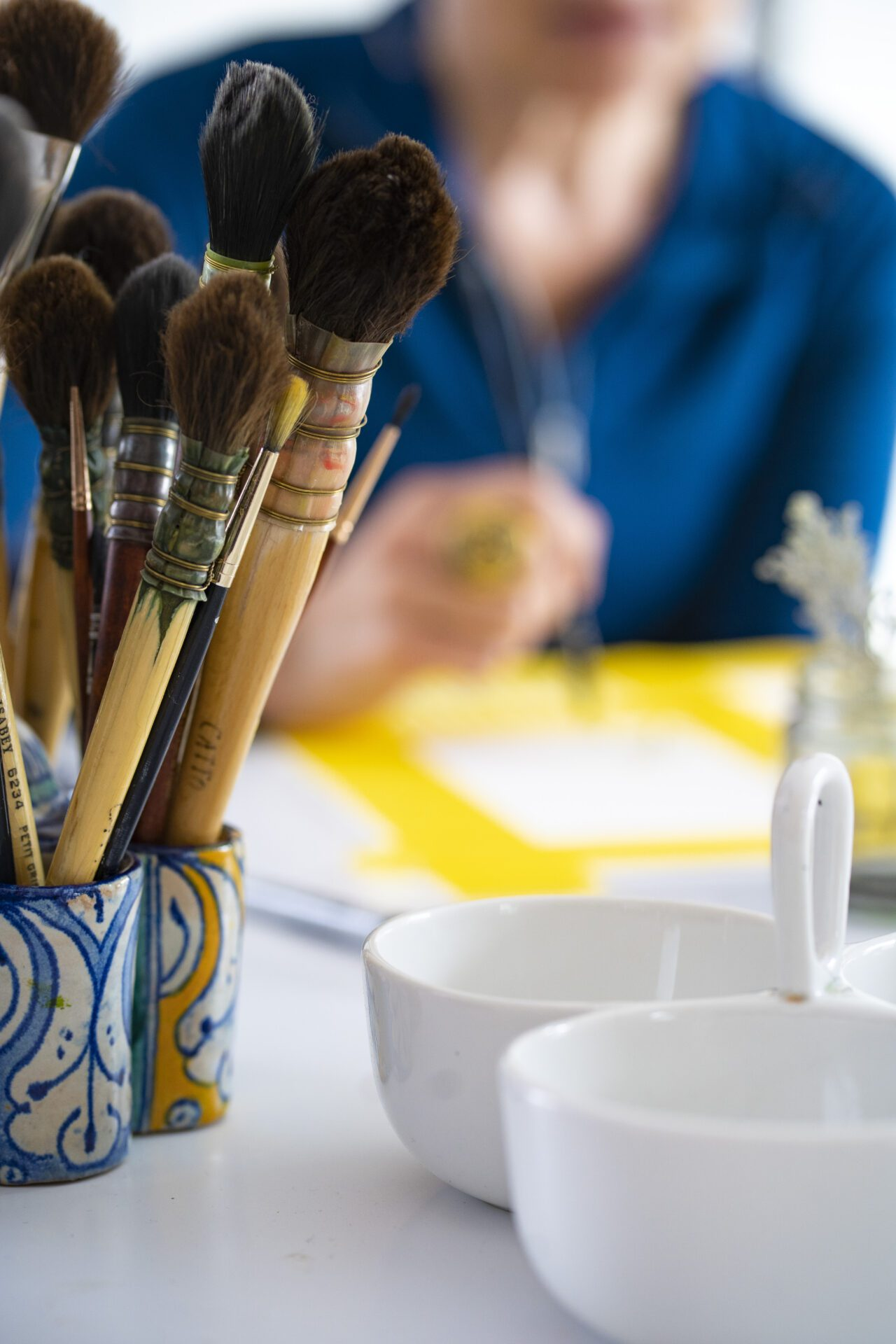 paintbrushes and bowls, isa working in background
