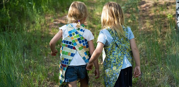 two young blonde girls with their backs to the camera wearing one blue green and tan geometric squares activity smock and another with a green and blue floral activity smock