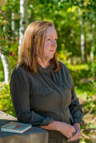 jennifer standing in garden leaning on a rock wall and looking out in the distance